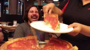 man laughing while cheesy pizza is being served