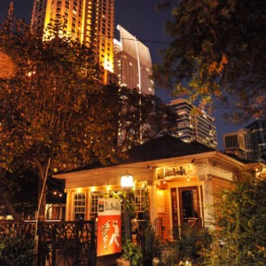 small residential looking restaurant in front of high rise buildings